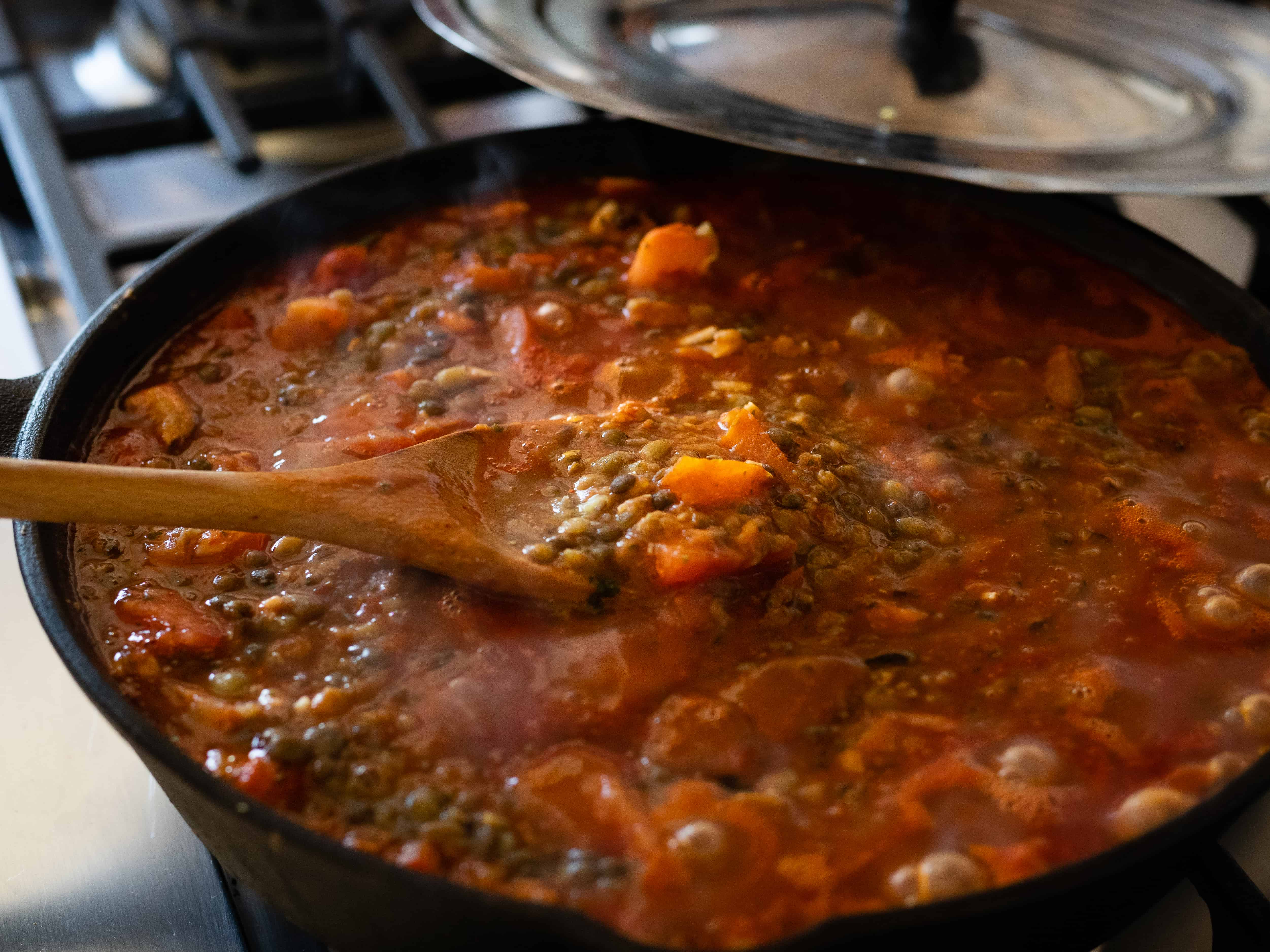 Cast iron pot with a lentil tomato sauce being cooked with a wooden spoon mixing it