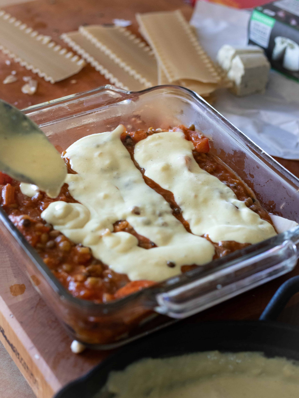 gluten free vegan lasagna being assembled, cheese sauce being poured onto lasagna