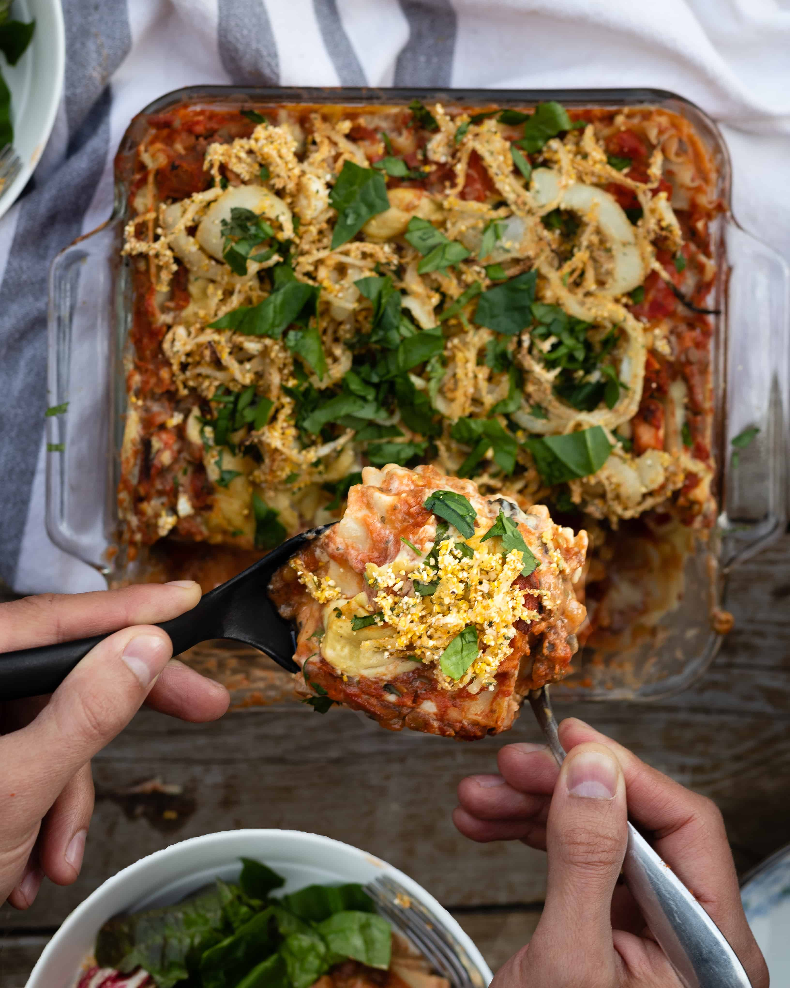 Birds eye view of vegan gluten free lasagna being served from a glass dish