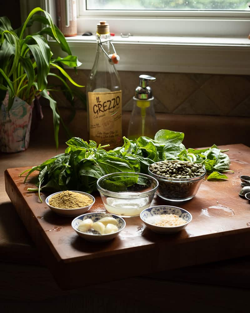 View of ingredients for a vegan pesto sauce on a wooden cutting board