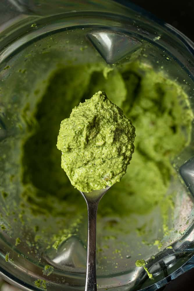 Birds eye view of creamy nut and oil free vegan pesto sauce on a spoon