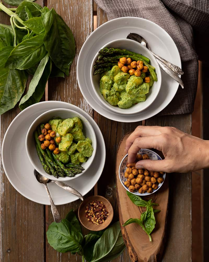 top down view of a dinner table with bowls of creamy gnocchi pesto with chickpeas and asparagus and a hand eating