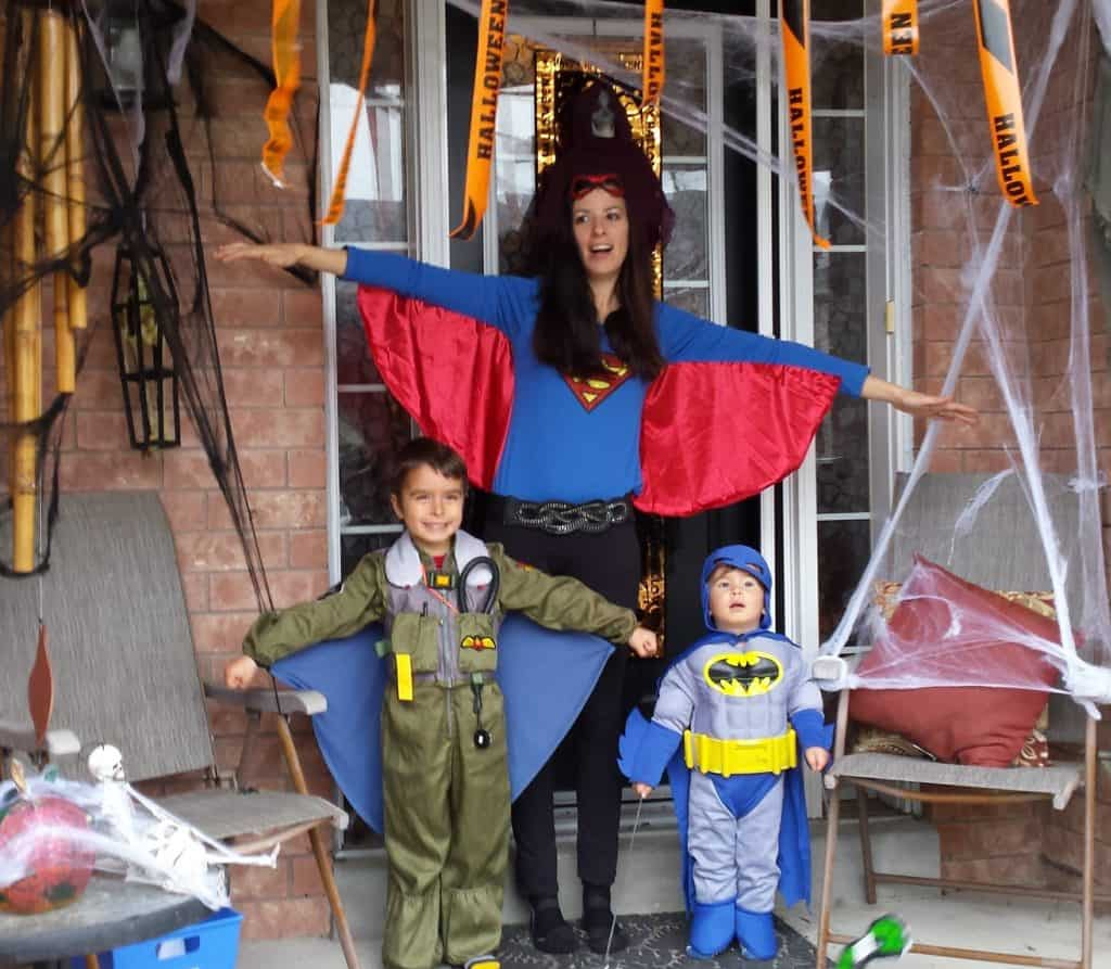 FAmily wearing halloween costumes standing in decorated porch
