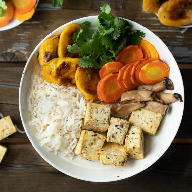 bowl of cooked tofu rice and fresh veggies on a wooden table