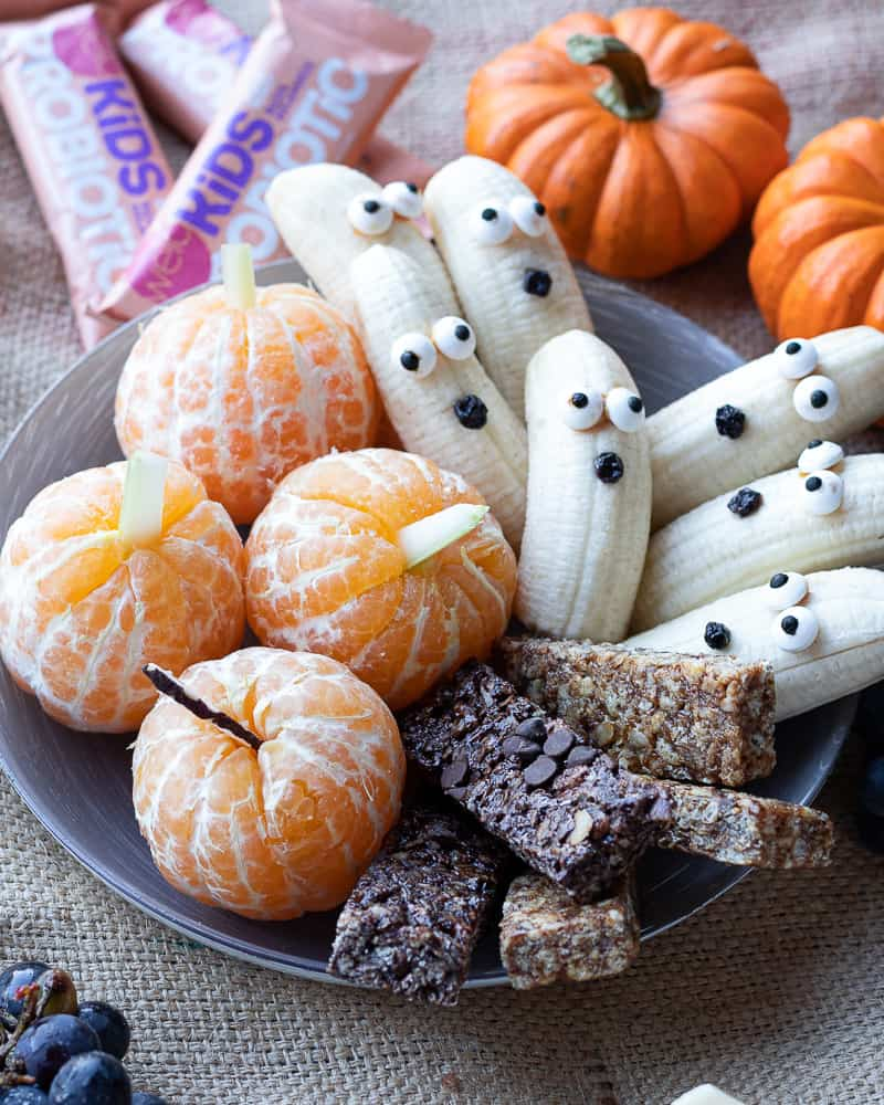 plate of Halloween snack ideas for kids with banana ghosts and tangerine pumpkins