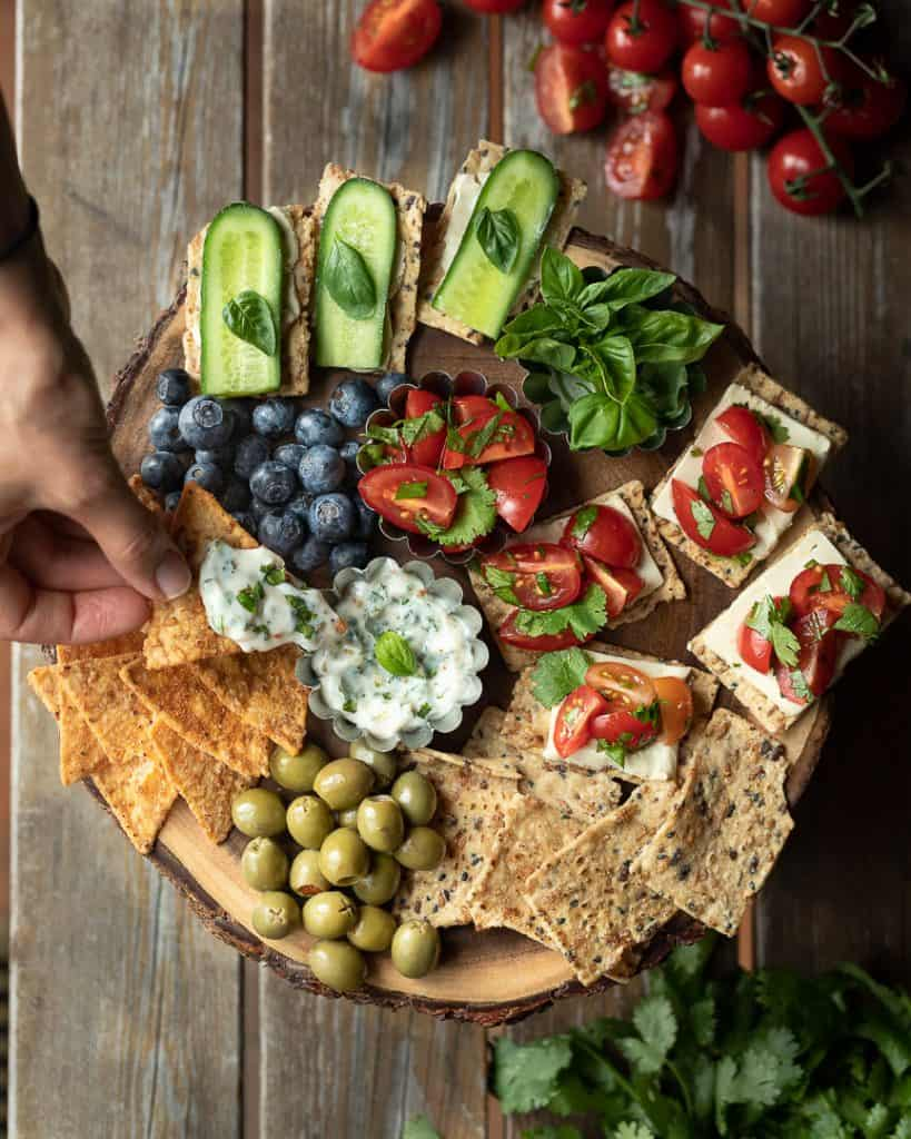 Dipping chip into dip on a snack platter