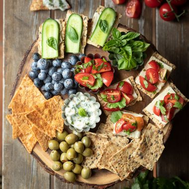 Snack tray with crackers, veggies and dips on wooden table