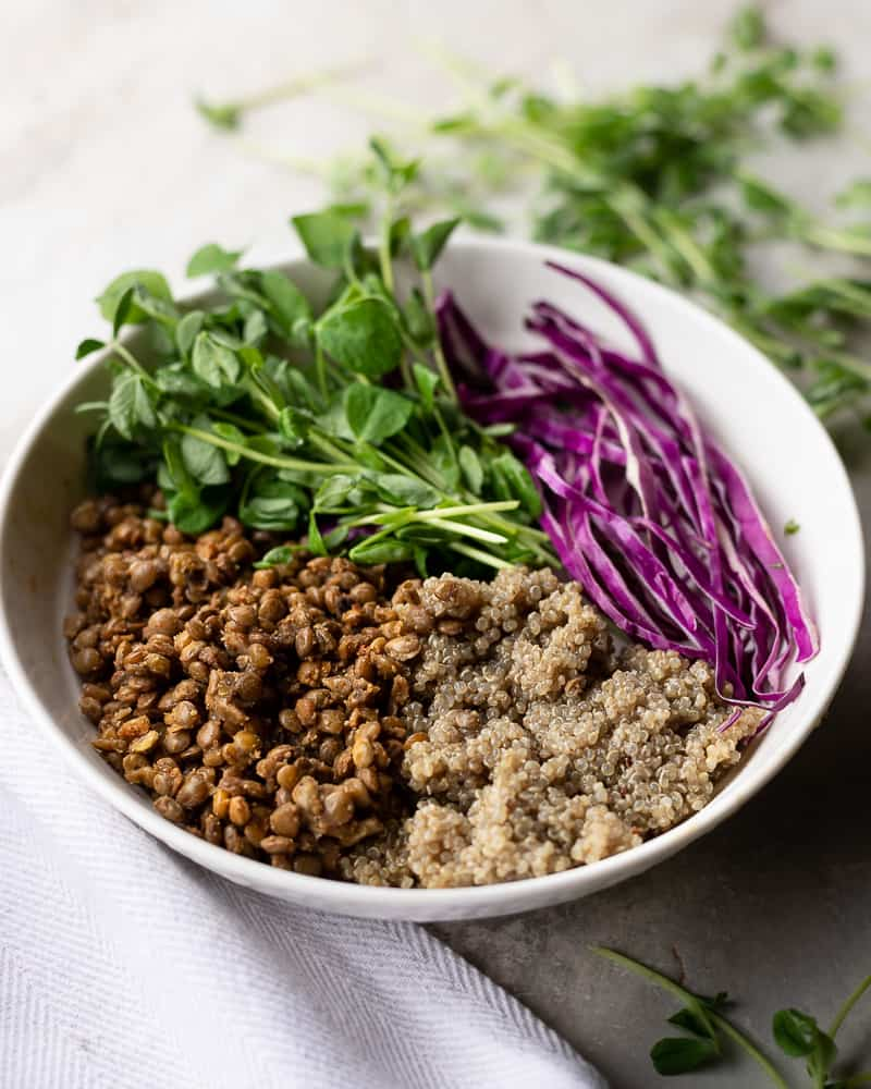 bowl of lentils, quinoa and spouts on a table
