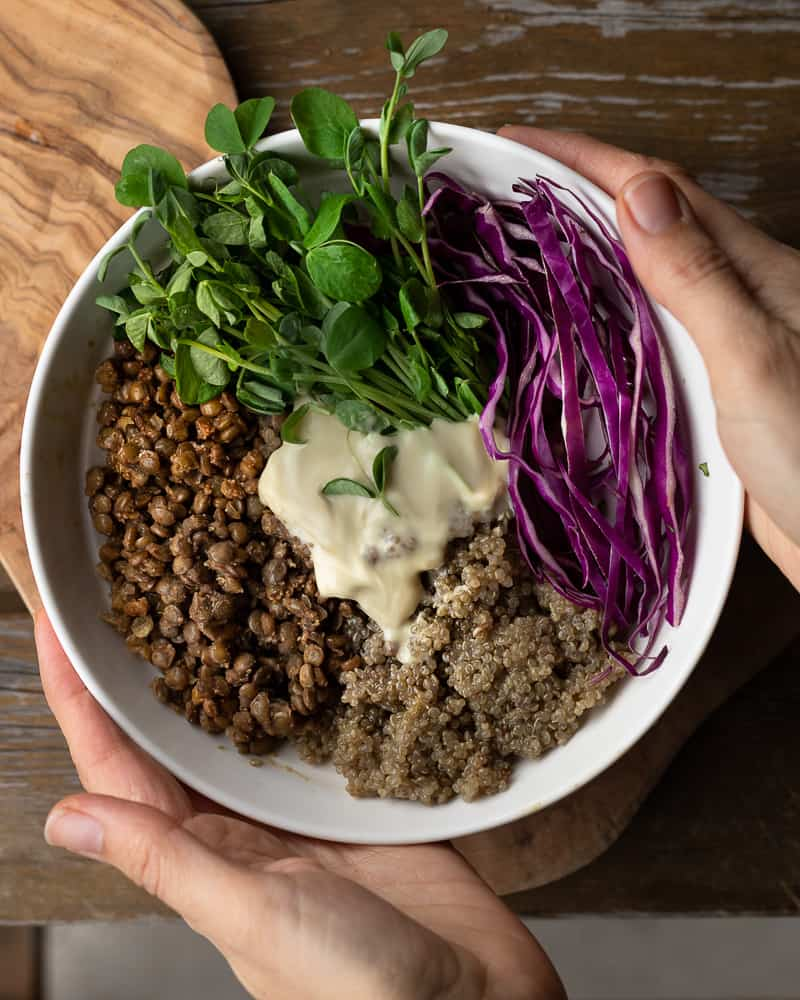 Bowl of spiced lentils and vegan cream sauce being held on a  wooden table