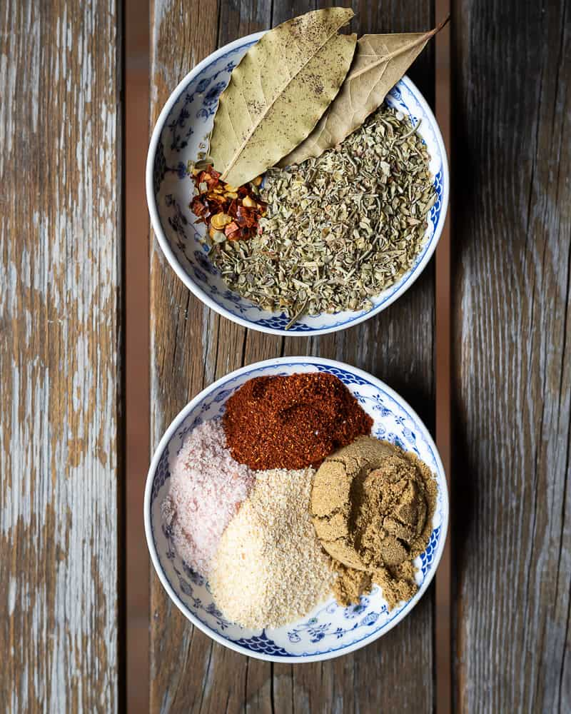 Wooden table with two small bowls of spices including bay leaves, Italian seasoning, salt, paprika, cumin