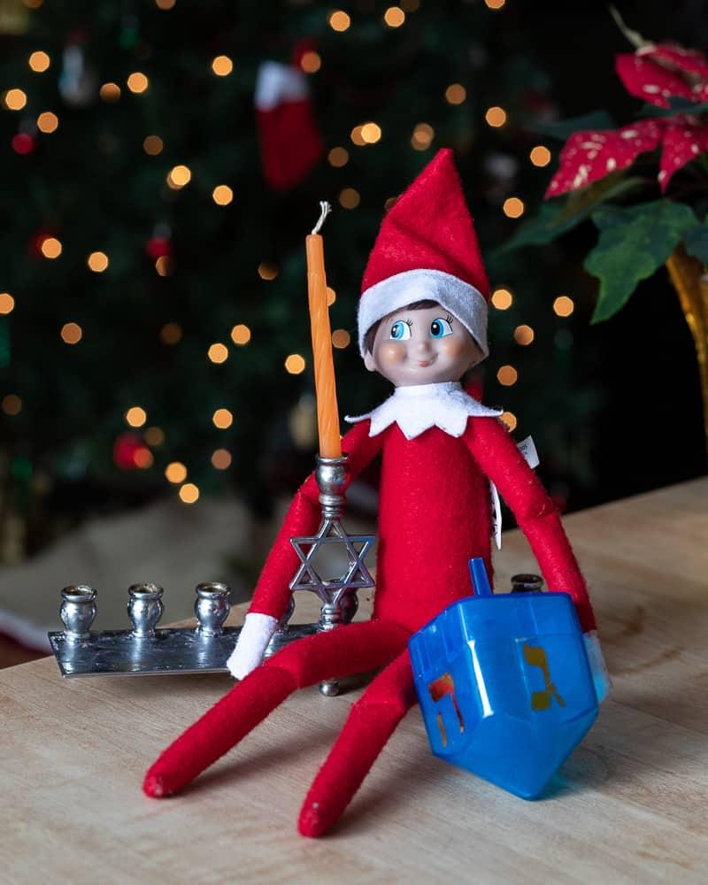 Elf on a shelf on a menorah holding a dreidel for a post on interfaith families