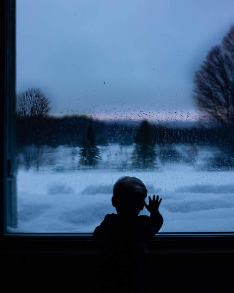 child watching the snow fall from a window