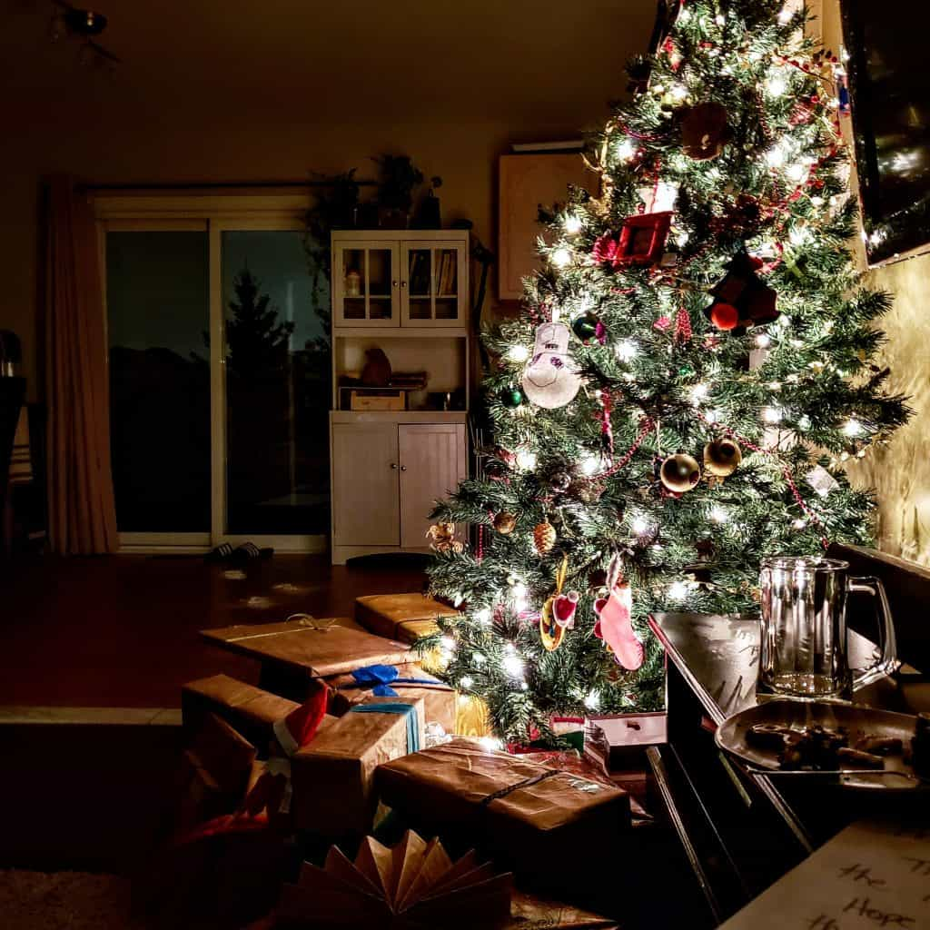 Straight view of a christmas tree with presents underneath for a post on interfaith marriage