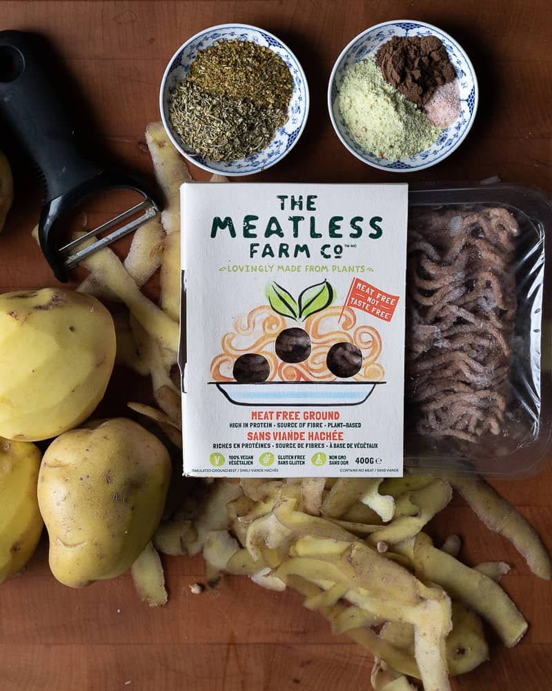 Top down view of the ingredients to make a vegan Shepherd's pie recipe> Whole white potatoes, vegan mock meat and spices on a wooden cutting board.