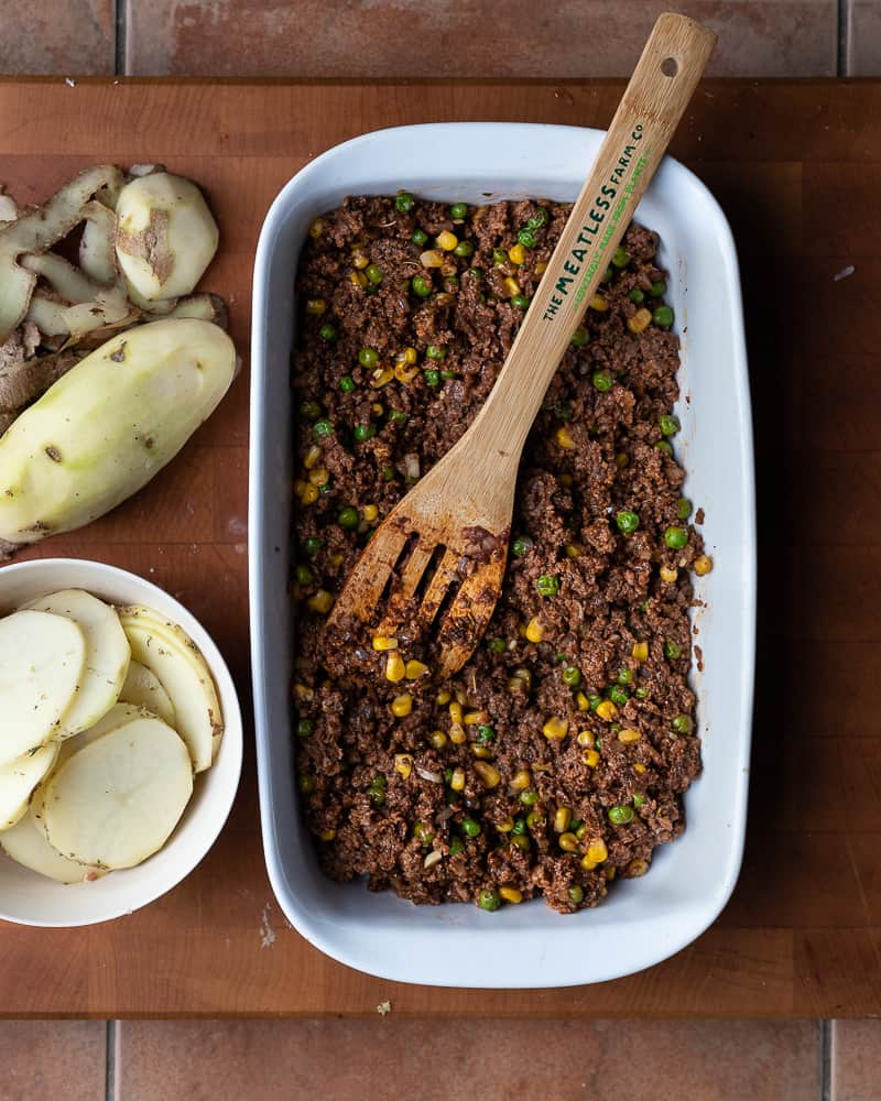 Baking dish with a vegan meat sauce layer surroundede by cut potatoes on a wooden cutting board