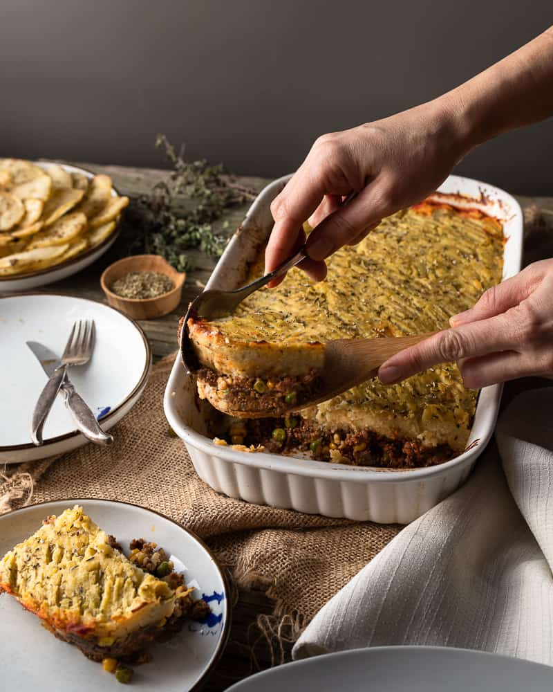 45 angle shot of vegan shepherds pie being served on a wooden dinner table