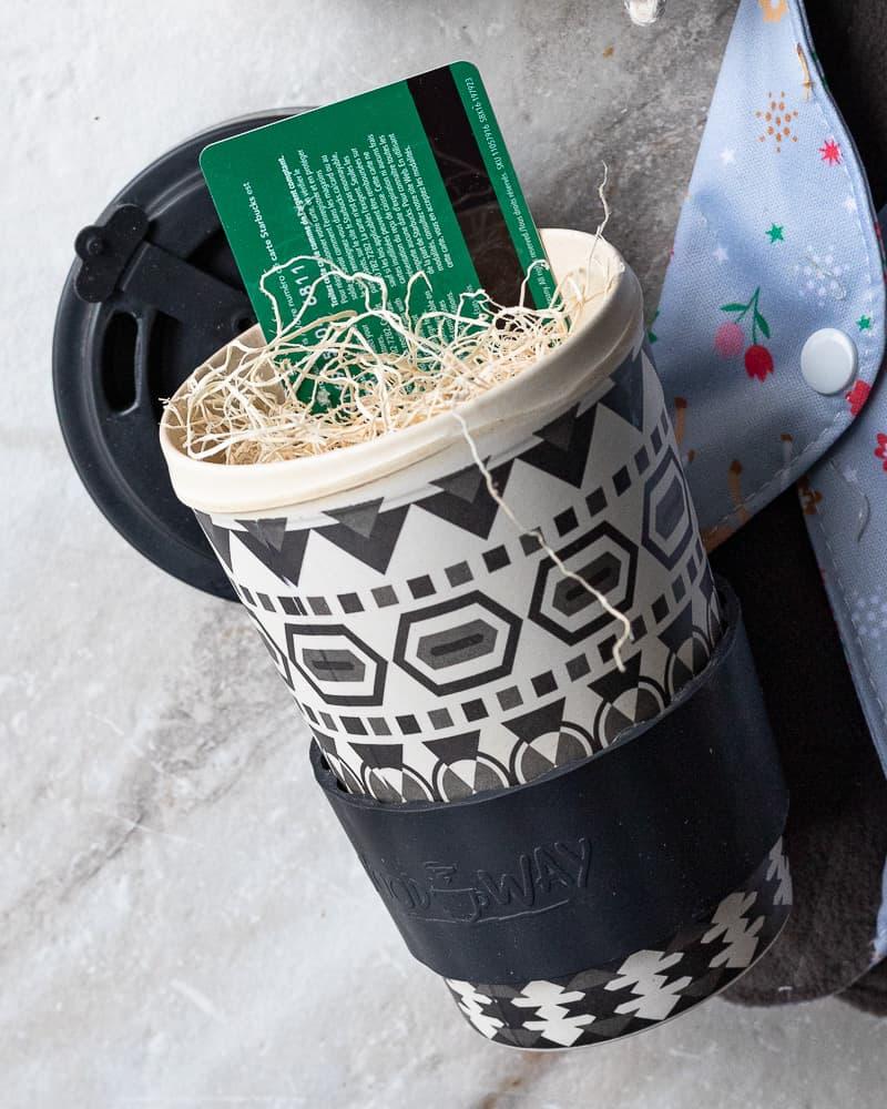 bamboo reusable coffee mug with a gift card inside