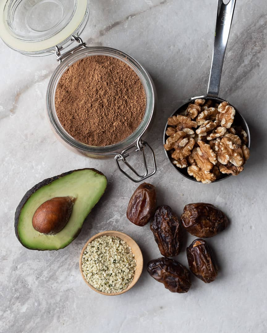 a marble table with ingredients to make fat bomb keto energy balls. Bowls of walnuts, avocado, cocoa powder, dates and hemp seed