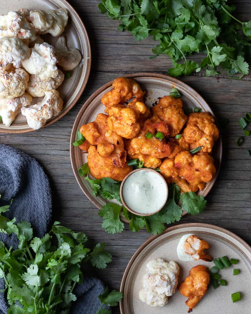 Top down view of 2 plates with cauliflower wings surrounded by fresh cilantro on a wooden table