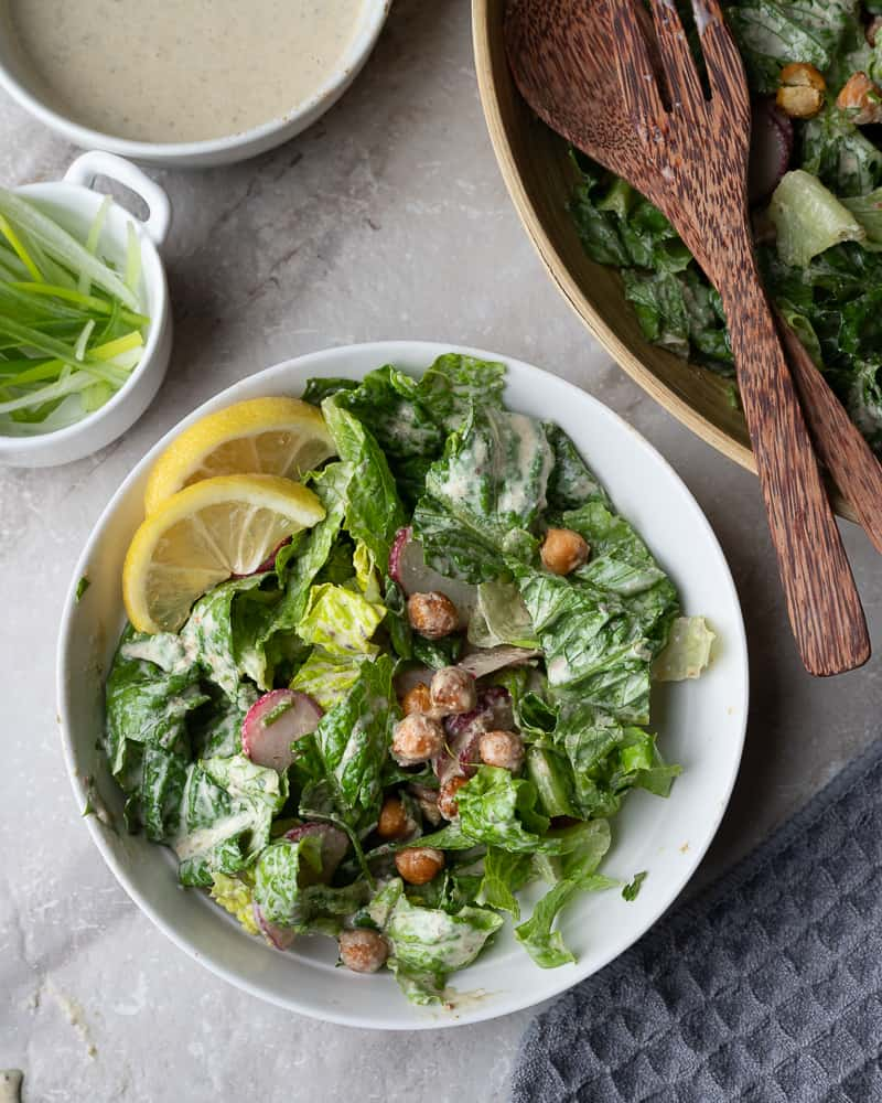 Bowl of creamy vegan caesar with sliced lemon and chickpeas on the dinner table