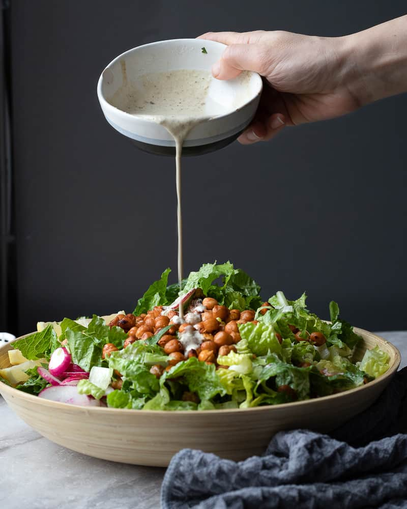 Creamy vegan tahini Caesar dressing being poured onto a romaine salad