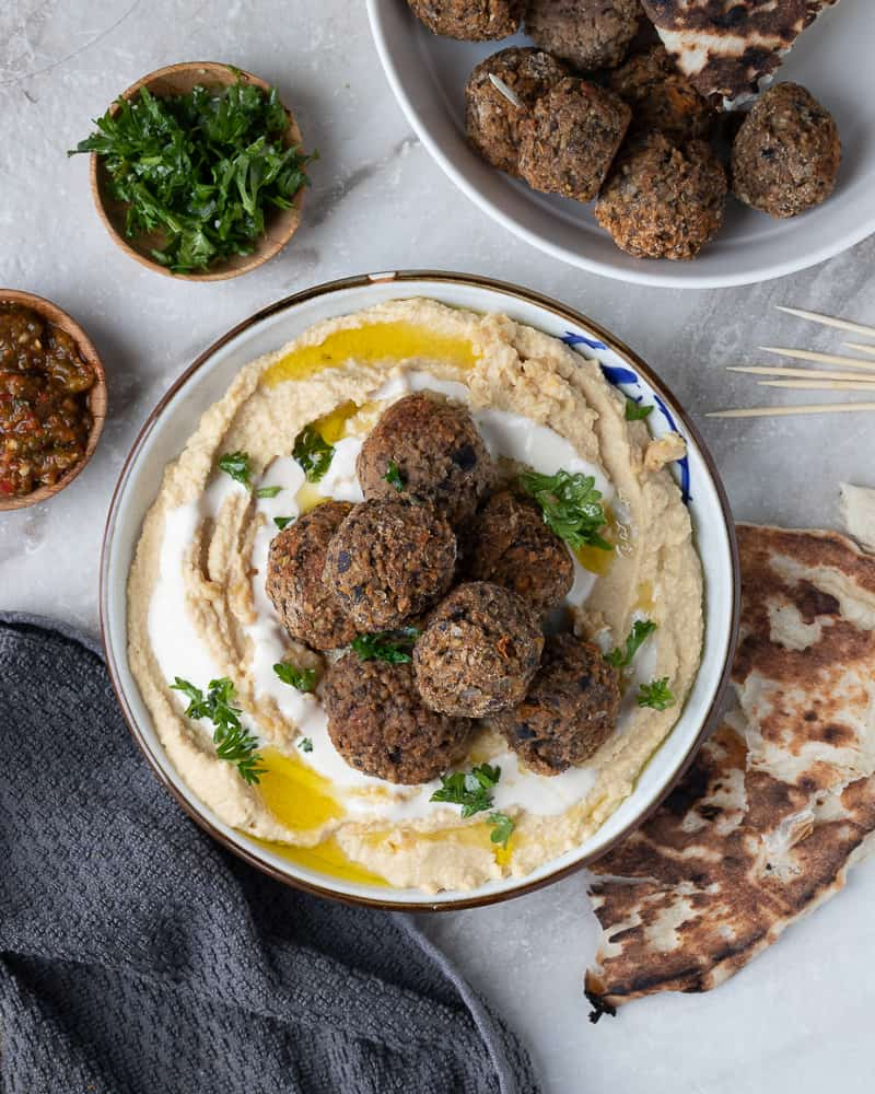 A big bowl of hummus topped with meatless meatballs surrounded by hot sauce and parsley
