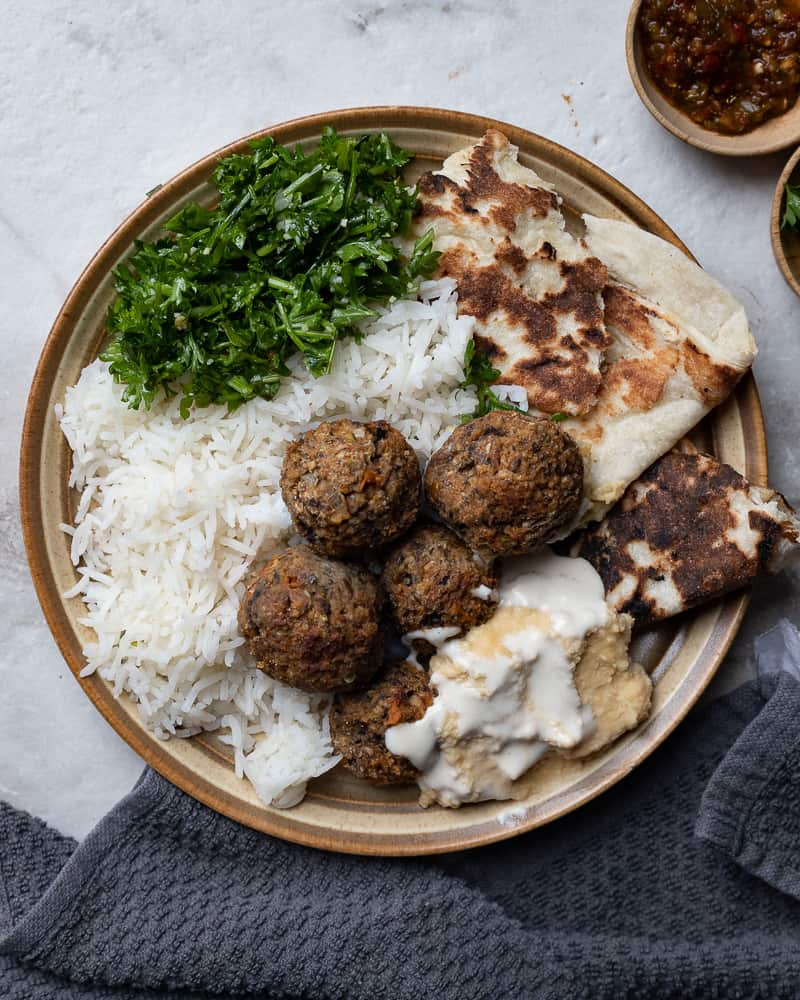 Plate with rice, pita bread, meatless meatballs and hummus on a marble table