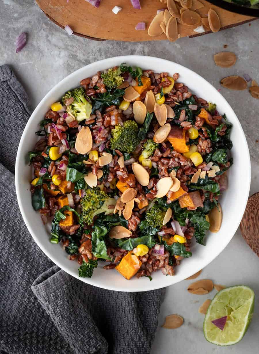 bowl of red rice salad with roasted veggies on a marble table with a gray napkin