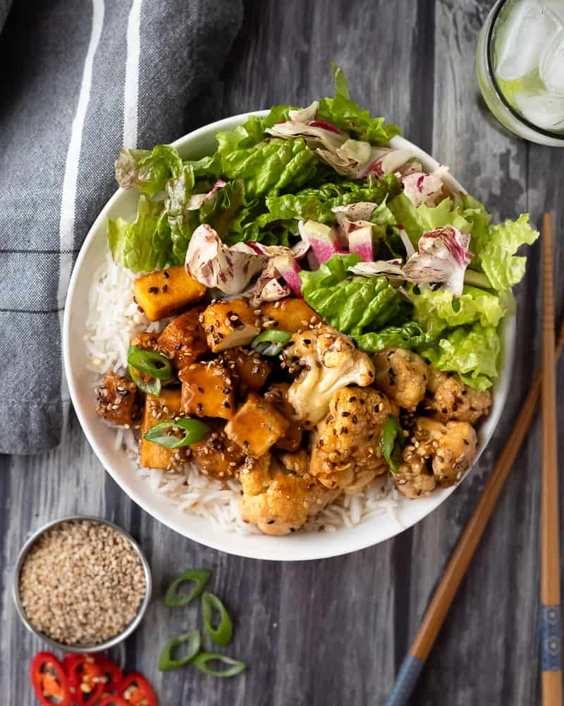 Bowl of saucey sesame tofu with salad and rice