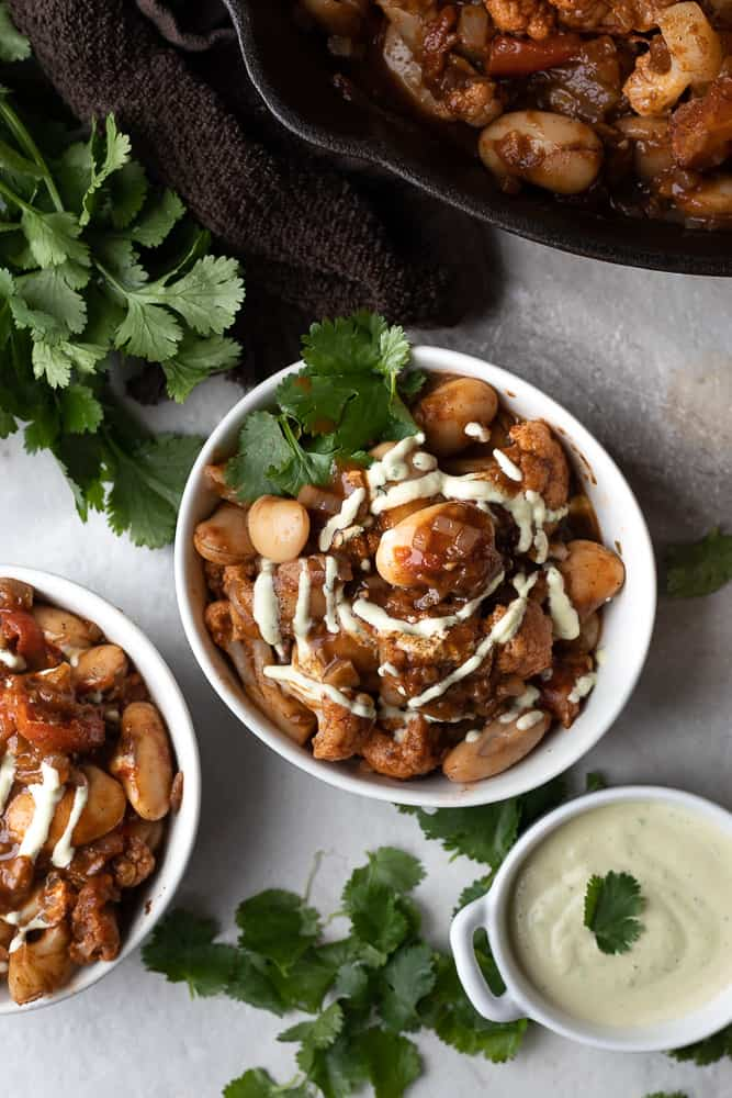 bowls on easy Morrocan white bean stew on the dinner table with small bowl of cilantro creme
