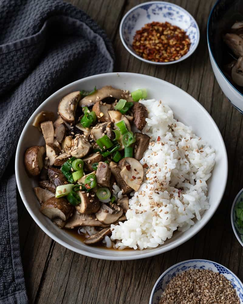 bowl of sauteed mushrooms with rice and green onions on a wooden table