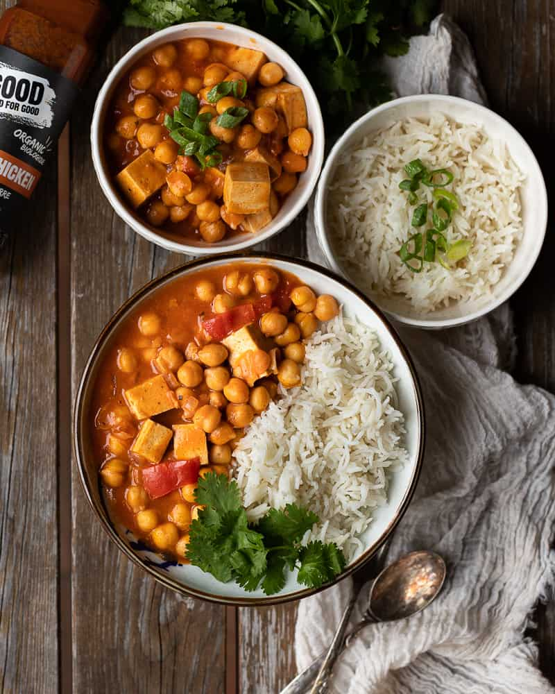 top down view of a bowl of vegan butter chicken with 2 smaller bowl of rice and chickpeas and tofu on the side.