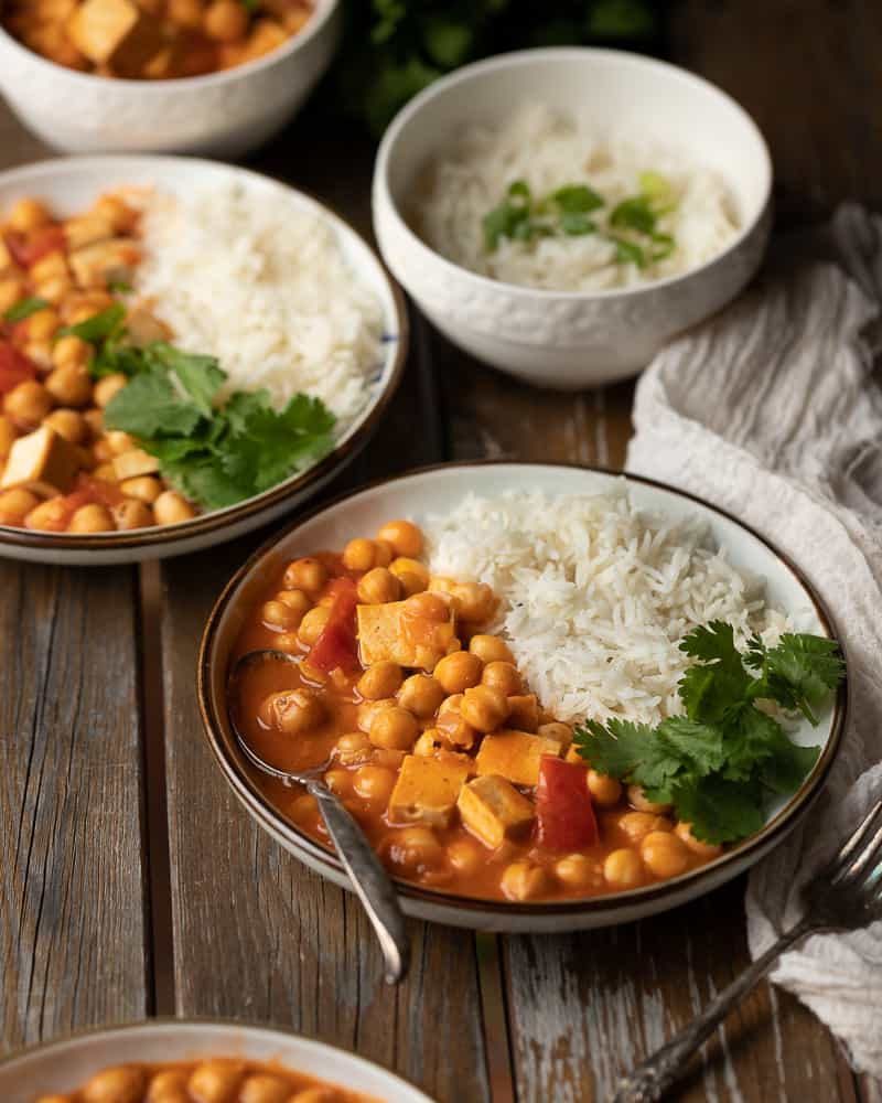 45 degree of a bowl of vegan butter chicken with tofu and chickpeas with a side of rice