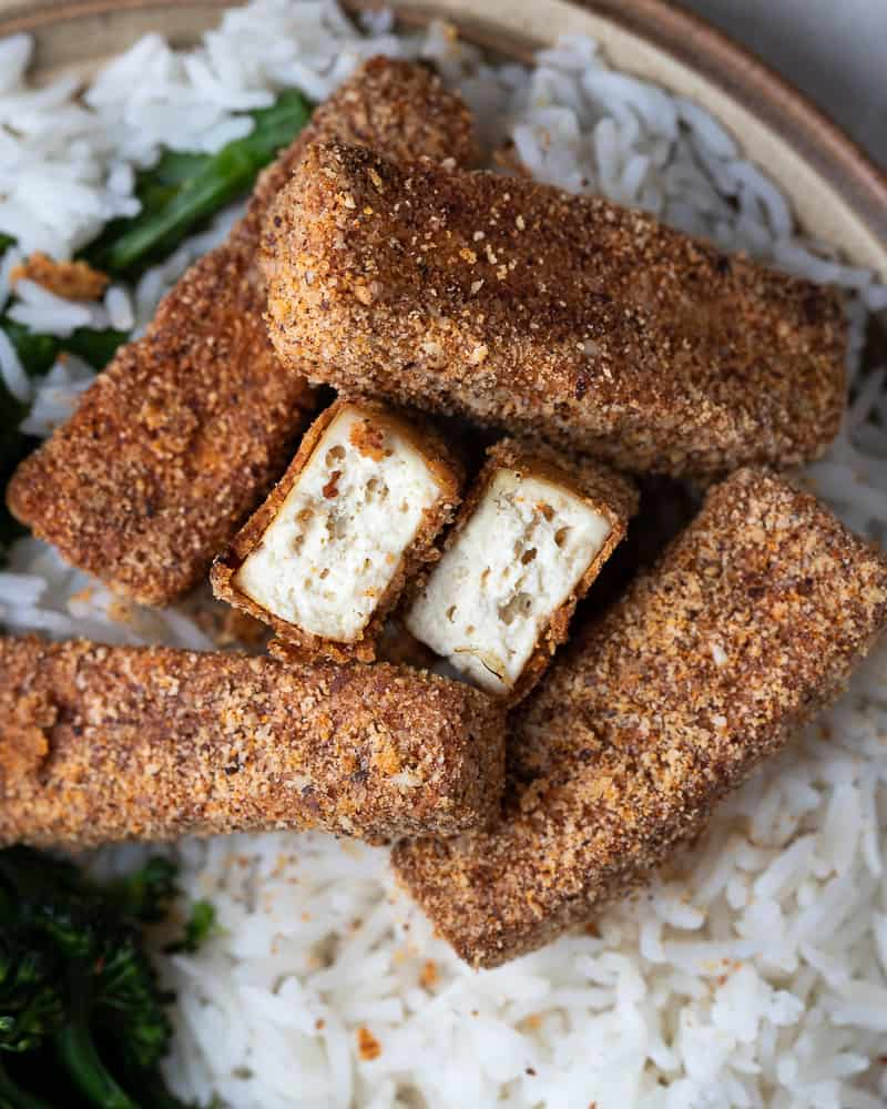 Top down view of crispy gluten free vegan chicken fingers on a bed of rice