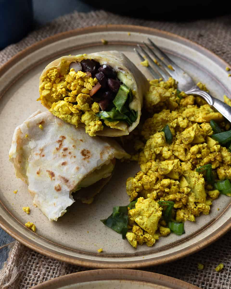 45 degree view of a breakfast burrito made with tofu scramble with tofu scramble on the side on a brown plate