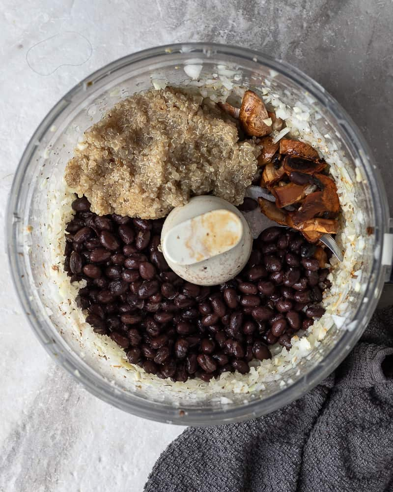 Birds eye view of black beans, mushrooms and quinoa in a food processor