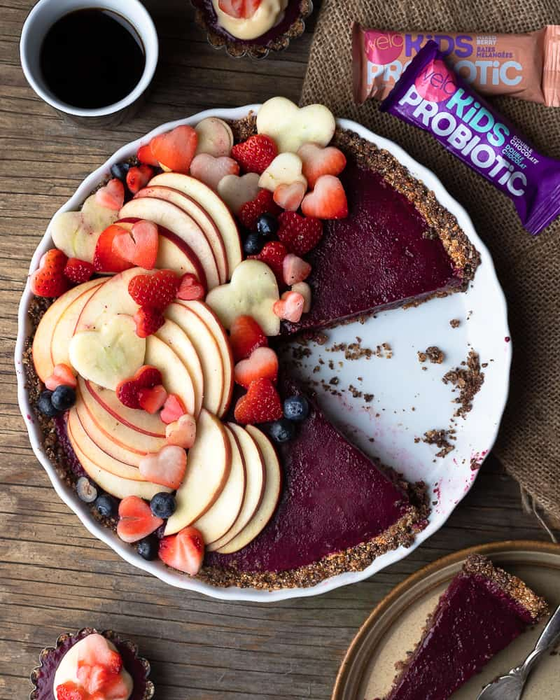 Top down view of vegan no bake berry pie with fresh sliced fruit on top and a coffee on the side
