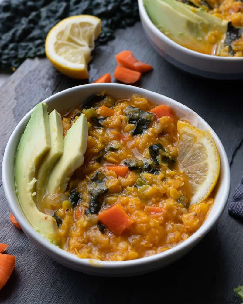 Close up shot of a bowl of red lentil, carrot and spinach stew topped with avocado