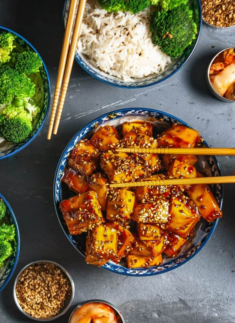 Top down view of a bowl of orange sesame tofu being served with chop sticks.