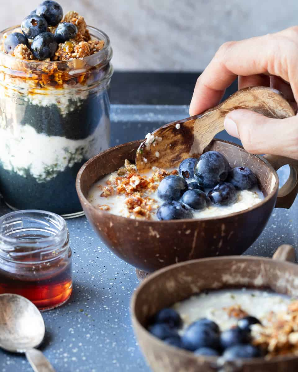Angel shot of a coconut bowl of overnight oats topped with fresh fruit and granola being eaten with a wooden spoon