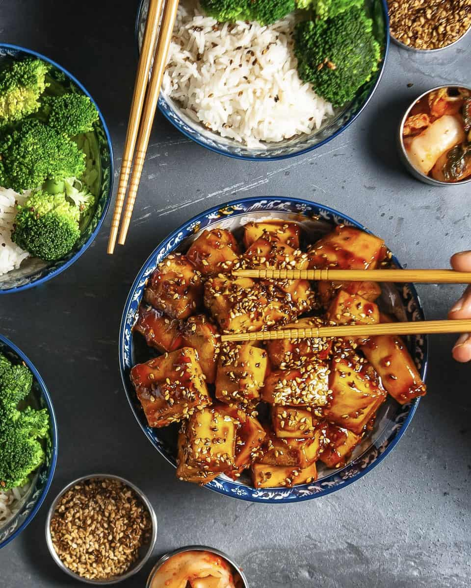 Top down view of an easy recipe with tofu. Bowls of sticky orange sesame tofu, rice and brocolli.  A crowd pleasing tofu dish for a easy vegan and gluten free recipe