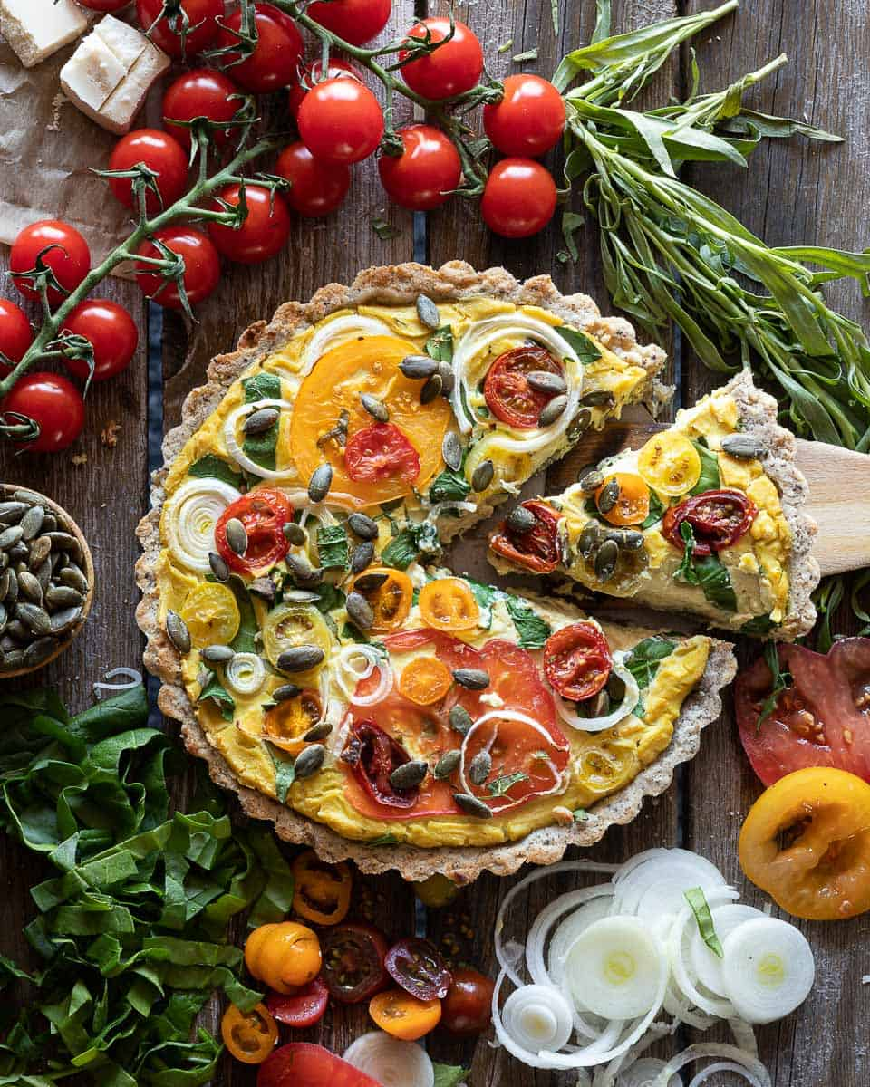 Top down view of a vegan quiche pie made with a gluten free vegan crust being served. Surrounded by fresh tomatoes, seeds and spinach