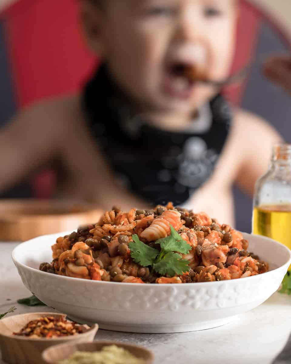 Straight shot of a bowl of delicious vegan lentil bolognese with a baby eating some in the background
